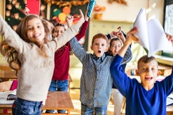 Large group of happy elementary students having fun while celebrating the end of a school year in th...