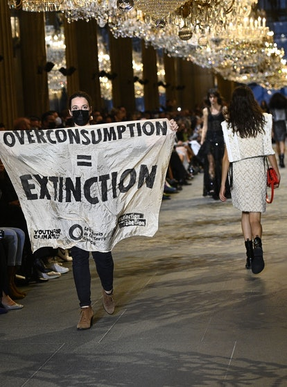 A demonstrator holds a banner as models present creations by Louis Vuitton during the Women's Spring...