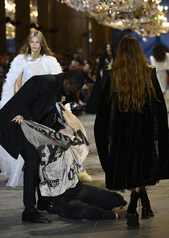 A demonstrator is being evicted by a security member as models present creations by Louis Vuitton du...
