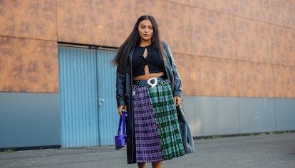 PARIS, FRANCE - SEPTEMBER 30: Model Paloma Elsesser wears a black trench coat, black croptop, green ...