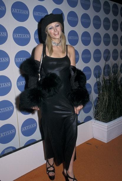 Paris Hilton wearing a black cowboy hat, slip dress, and fur coat in 2000.