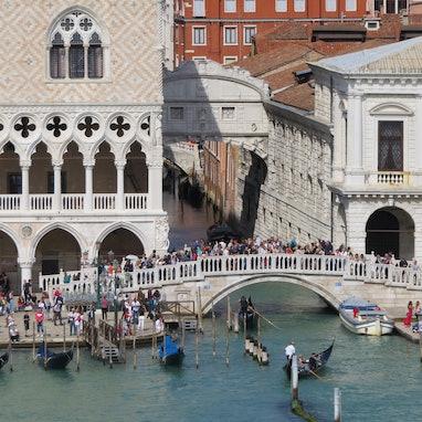 September 20, 2019 - Venice, Italy: Gondolas pass under a bridge where tourists are gathered to take...