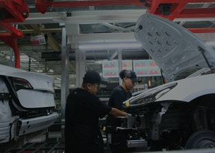 Production associates work on a Tesla Model 3 at the Tesla factory on Wednesday, July 18,  2018 in F...
