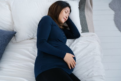 Image of a pregnant adult lying down in bed while resting a hand on the belly.