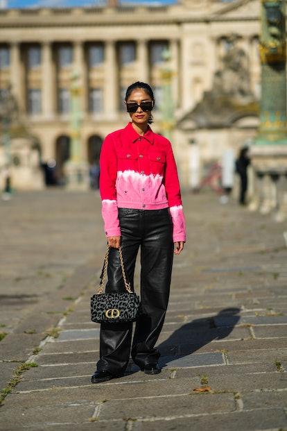 PARIS, FRANCE - SEPTEMBER 28: Pornwika Spiecker wears black sunglasses, gold earrings, a red / white...