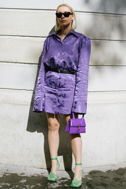 PARIS, FRANCE - SEPTEMBER 29: A guest poses wearing an Attico dress, Prada belt and Jacquemus bag af...