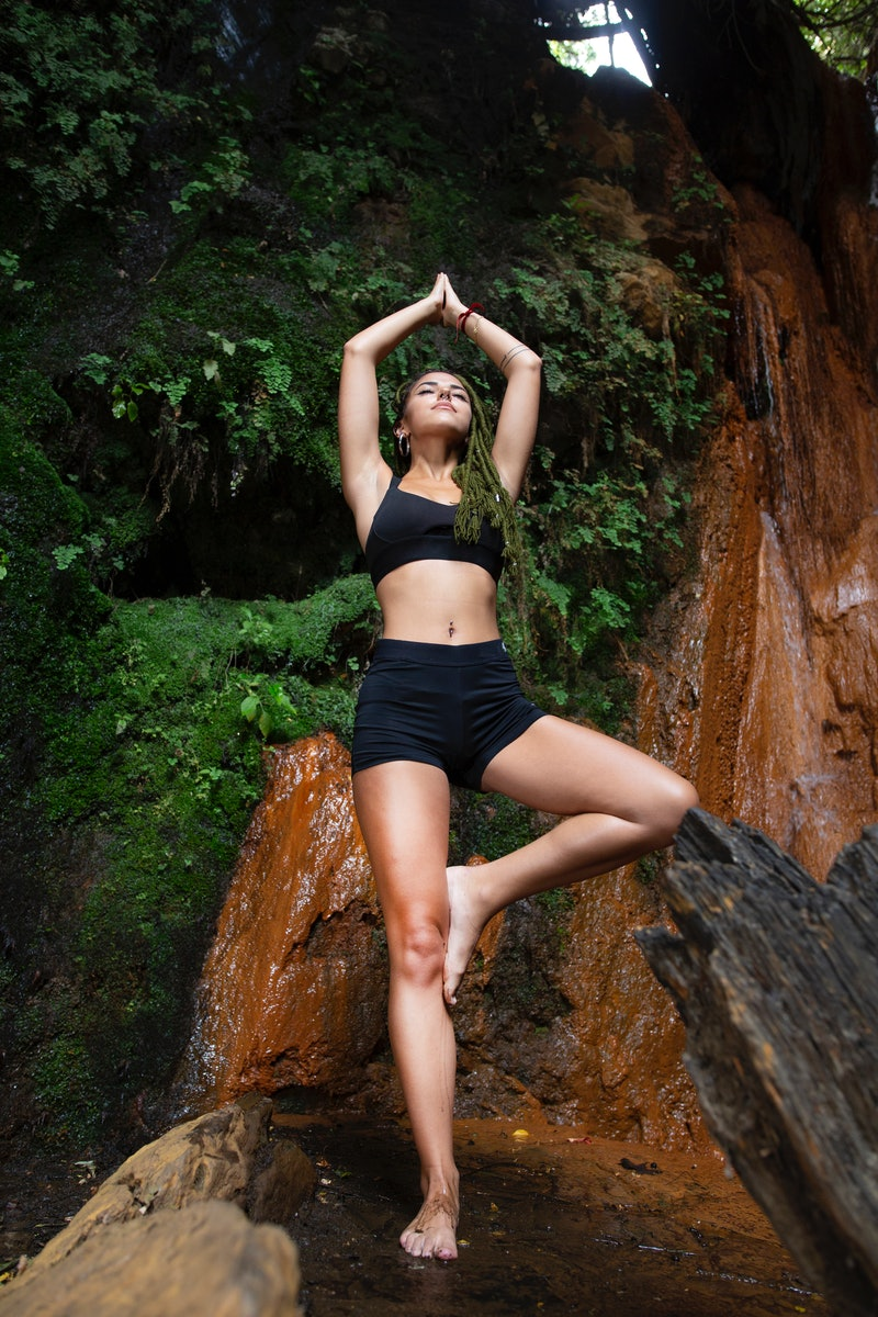 A woman in tree pose under a waterfall. The October new moon's spiritual meaning suggests a fresh st...