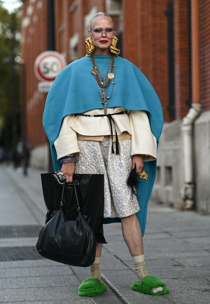 PARIS, FRANCE - SEPTEMBER 29: A guest is seen wearing a blue cape, vintage dress, green slippers, vi...
