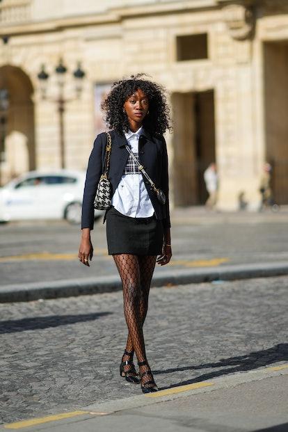 PARIS, FRANCE - SEPTEMBER 28: Emmanuelle Koffi wears gold large earrings, a white shirt, a navy blue...