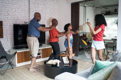 Teenager girl filming on smartphone family dancing together at home