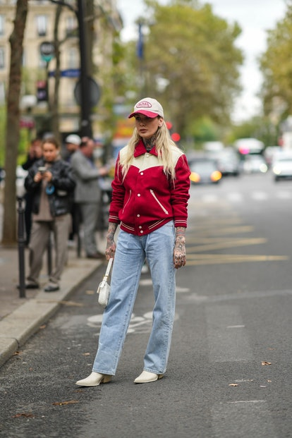 PARIS, FRANCE - OCTOBER 01: A guest wears a white and red ripped Von Dutch cap, silver earrings, a r...