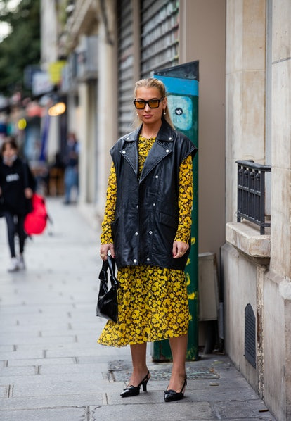 PARIS, FRANCE - SEPTEMBER 29: A guest is seen wearing black leather vest, yellow dress with floral p...