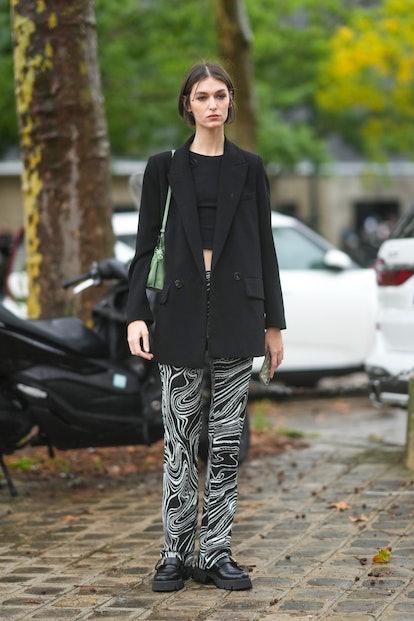 PARIS, FRANCE - OCTOBER 05: A guest wears silver earrings, a black cropped t-shirt, a black long bla...