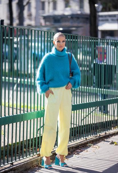 PARIS, FRANCE - OCTOBER 04: Leonie Hanne seen wearing blue knitted turtleneck, yellow pants, heels o...
