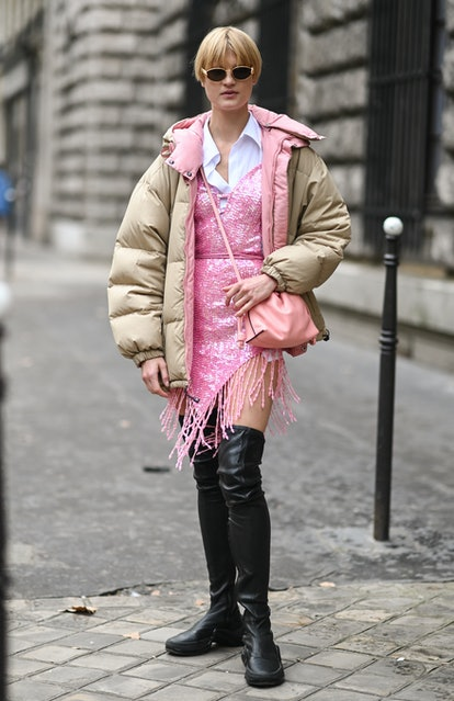 PARIS, FRANCE - OCTOBER 01: Model Michelle Laff is seen wearing a tan puff coat, pink dress and blac...
