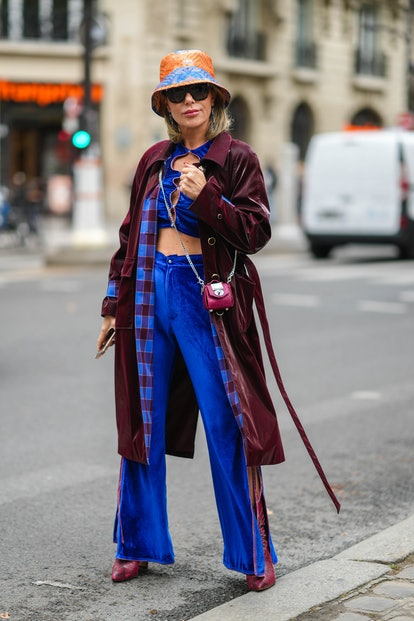 PARIS, FRANCE - OCTOBER 01: A guest wears a blue and orange print pattern bob / hat from Dawang, bla...