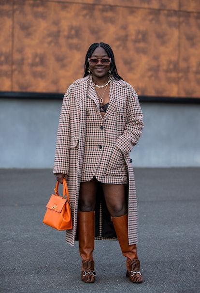 PARIS, FRANCE - SEPTEMBER 30: Lois Opoku seen waring checkered coat and blazer, orange bag, boots ou...