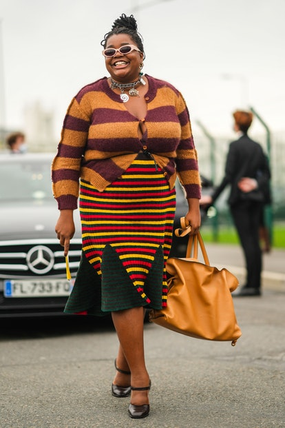 PARIS, FRANCE - OCTOBER 02: Gabriella Karefa-Johnson wears beige sunglasses, gold earrings, a silver...