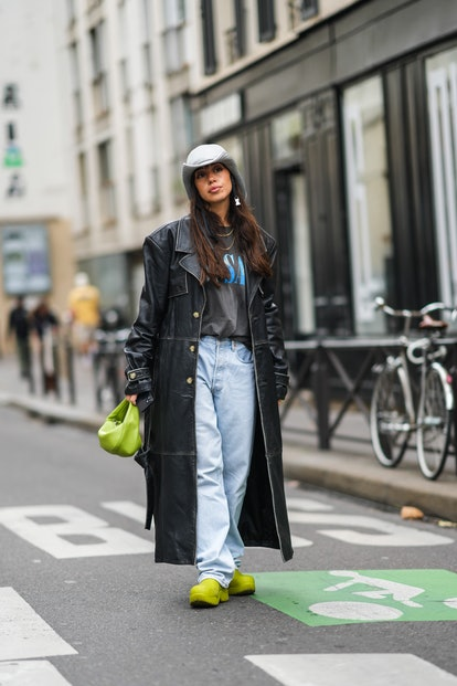PARIS, FRANCE - OCTOBER 02: A guest wears a gray hat, silver earrings, gold chain necklaces, a black...