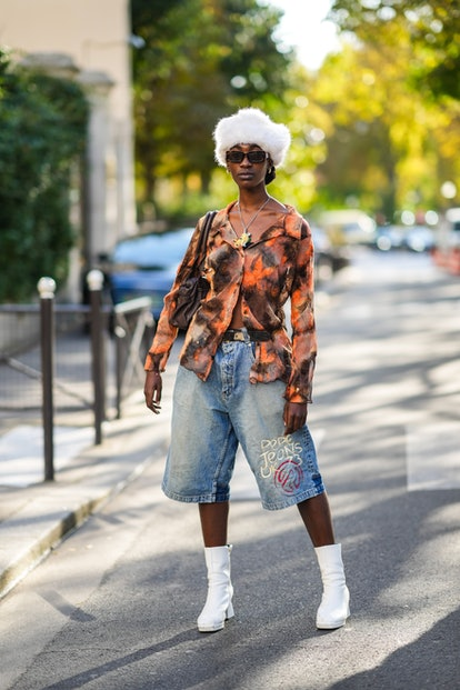PARIS, FRANCE - SEPTEMBER 28: A guest wears gold earrings, a white fluffy hat, black sun glasses, a ...