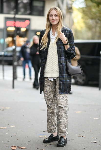 PARIS, FRANCE - OCTOBER 03: A guest is seen wearing a plaid jacket, cream sweater and camo pants out...