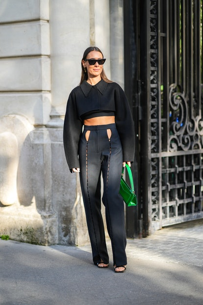 PARIS, FRANCE - SEPTEMBER 28: Alice Barbier wears black sunglasses, a black cropped t-shirt, a black...