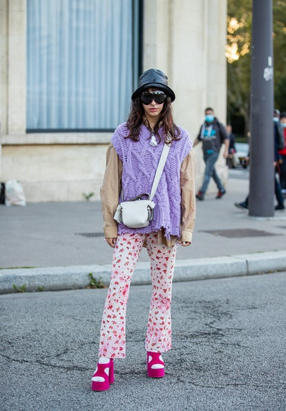 PARIS, FRANCE - SEPTEMBER 29: A guest is seen wearing yellow knitted slip over, bag, hat, sunglasses...