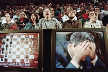 Chess enthusiasts watch World Chess champion Garry Kasparov on a television monitor as he holds his ...
