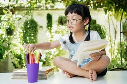 Asian student girl drawing and writing on the book for homework at home
