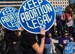 Women rights activists and advocates for abortion rights hold up signs as they gather at Freedom Pla...