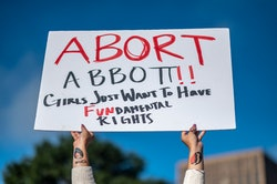 A woman holds a sign in reference to Texas Governor Greg Abbott as protesters take part in the Women...