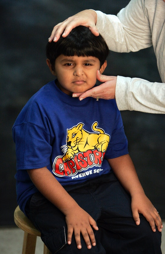Joshua Baptista, a 1st grader, has his head posed into the proper position before being photographed...