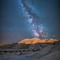 The lights from the train that runs through the Oglala National Grassland light up the badlands of T...