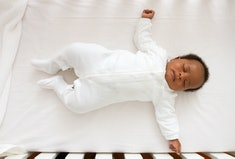 Baby sleeping on its back in a crib