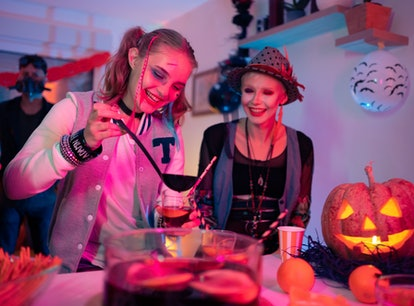 Female friends having fun and drinking TikTok drinks inspired by Halloween movies at the Halloween p...
