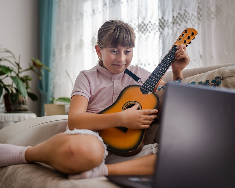 Little girl taking guitar lesson online and playing guitar against laptop
