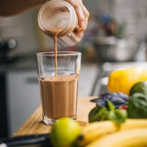 A woman prepares a smoothie using pre-workout powder. On TikTok, people are dry-scooping pre-workout...
