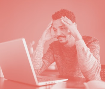 Worried or tired man working using laptop at home