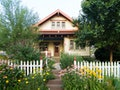 A typical suburban house with a white picket fence. One writer redefines home as a second-generation...