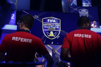 Referees monitor the play as players compete on Microsoft Xbox and Sony Playstation games consoles i...