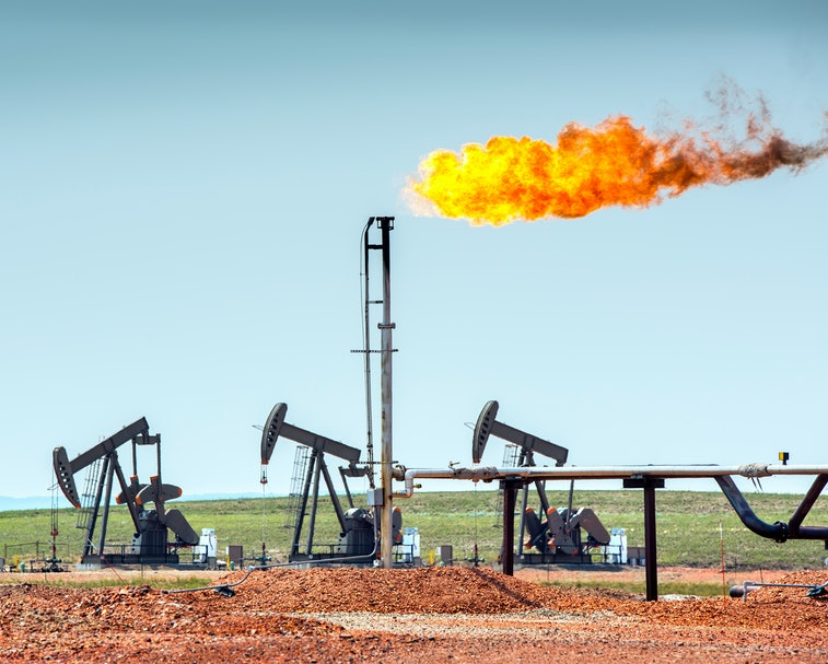 Oil well pumpjacks at work in the oil fields of North Dakota. The yellow flame is called flaring and...