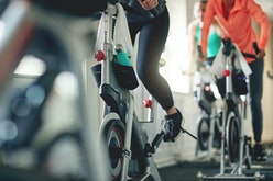 Cropped shot of women working out with exercise bikes in a exercising class at the gym