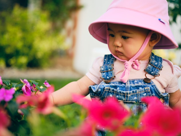 baby in pink hat looking at pink flowers