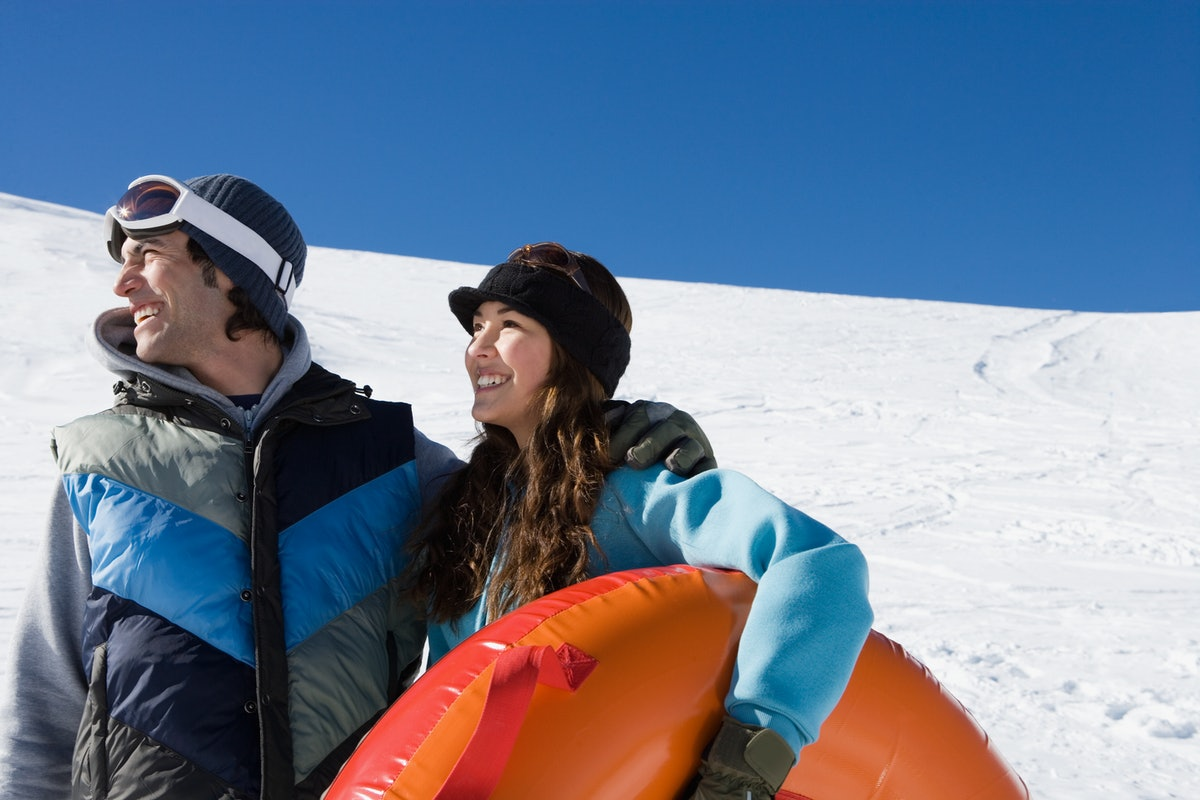 A happy couple smiles while looking off into the distance and holding a snow tube on a snowy hill.