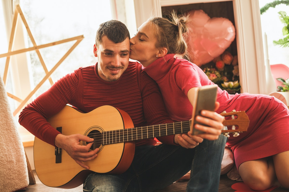 A loving couple in red and pink pose for a photo while playing the guitar on Valentine's Day.