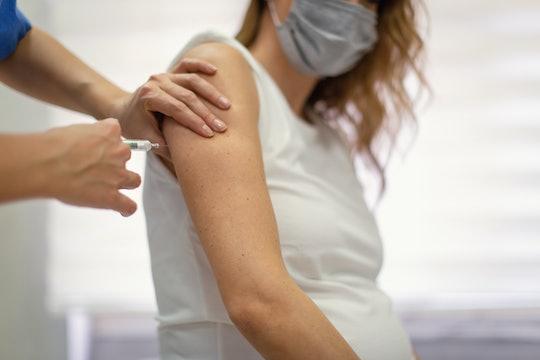 A pregnant woman receives a shot.
