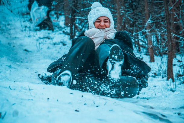 A happy woman slides down a hill in a snow tube.