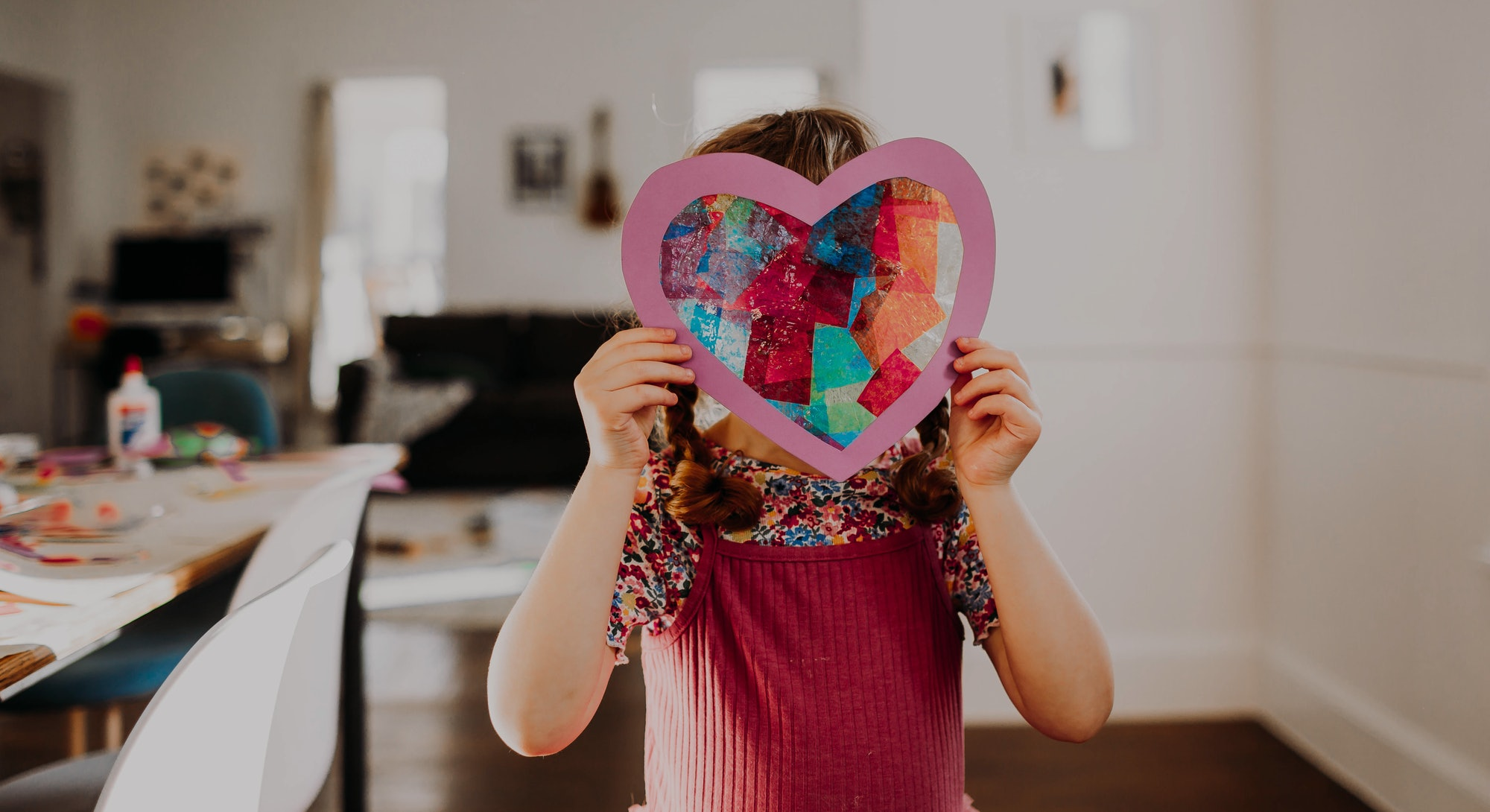 child holding up stained glass heart made from tissue paper