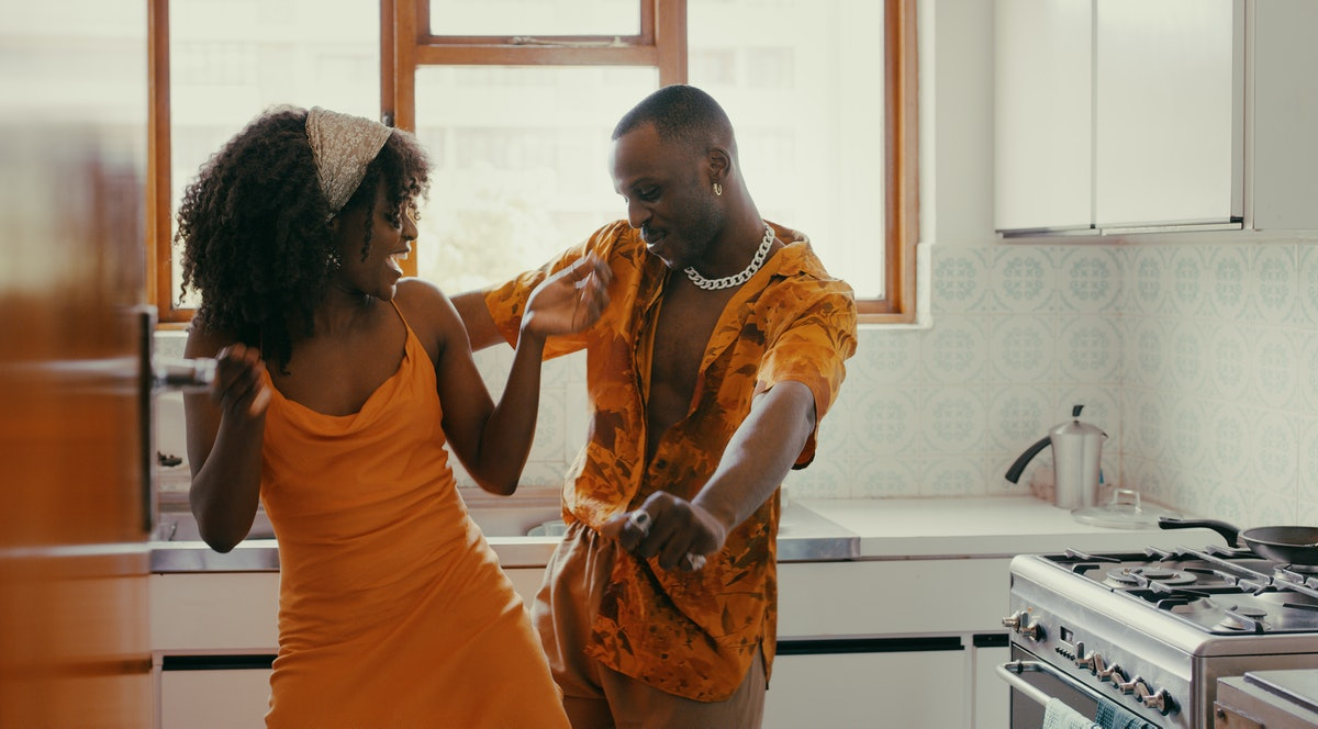 A couple in matching orange outfits dances and sings in the kitchen on Valentine's Day.