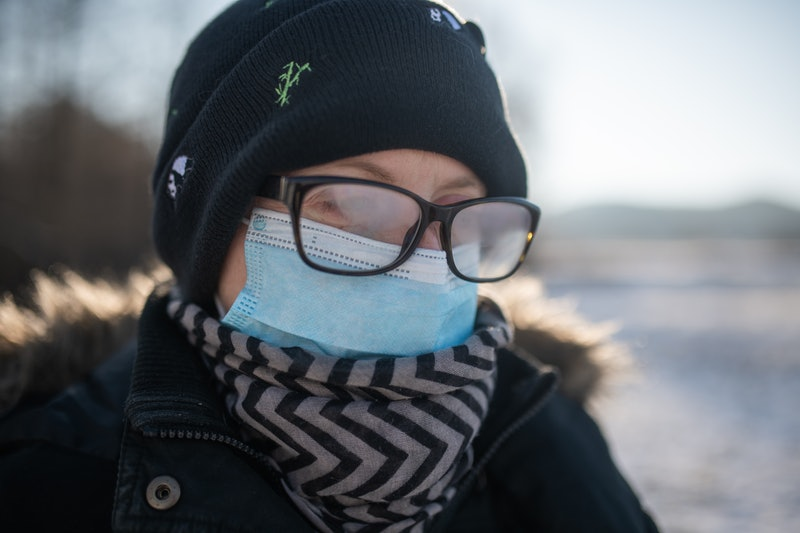 A person wears a winter coat, beanie, mask and glasses, with their glasses fogging up. There's a simple hack to prevent your mask from fogging up your glasses.